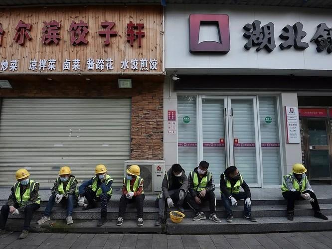 Công nhân ngồi bên ngoài một nhà hàng đã đóng cửa ở Vũ Hán, Trung Quốc ngày 23/2. Ảnh: AP