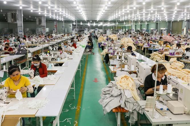Công nhân của Công ty GarmentTech Pro (Khu công nghiệp Tân Đô, huyện Đức Hòa, Long An) sản xuất khẩu trang vải. Ảnh: Quỳnh Trần.
