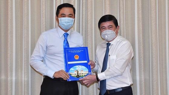 Chủ tịch UBND TP.HCM Nguyễn Thành Phong trao quyết định cho tân Giám đốc Sở Công thương Bùi Tá Hoàng Vũ. Ảnh: Việt Dũng