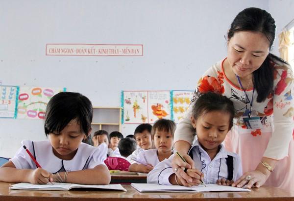 Cô tận tâm giảng dạy từng nét chữ cho học sinh lớp 1 (Ảnh: Báo Ninh Thuận)
