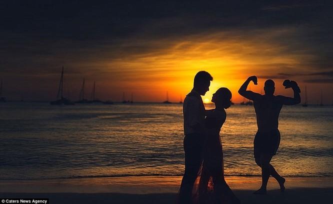 Vào chiều hoàng hôn lãng mạn, biển lặng yên không gợn sóng, cặp uyên ương nhìn nhau say đắm bên cạnh một người đàn ông đang... khoe cơ bắp.