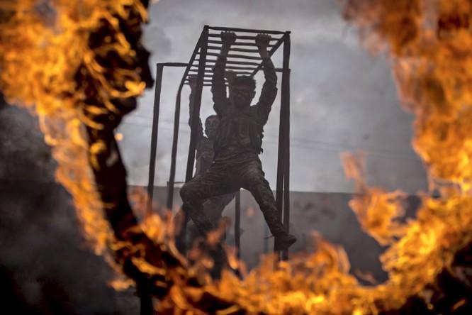 Ở Syria, các thành viên của lực lượng YPG của người Kurd luyện tập trên thanh khỉ và trở ngại lửa.