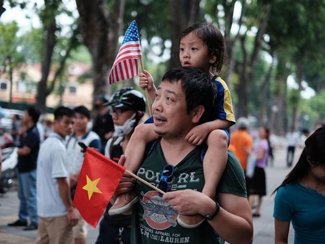 Một người cha và con gái đứng chờ đoàn xe chở Tổng thống Mỹ đi qua. (Ảnh: Getty Images)