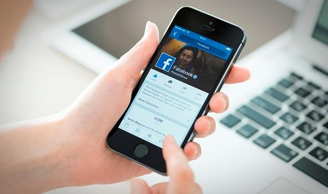 Người dùng lướt Facebook thay vì đọc báo