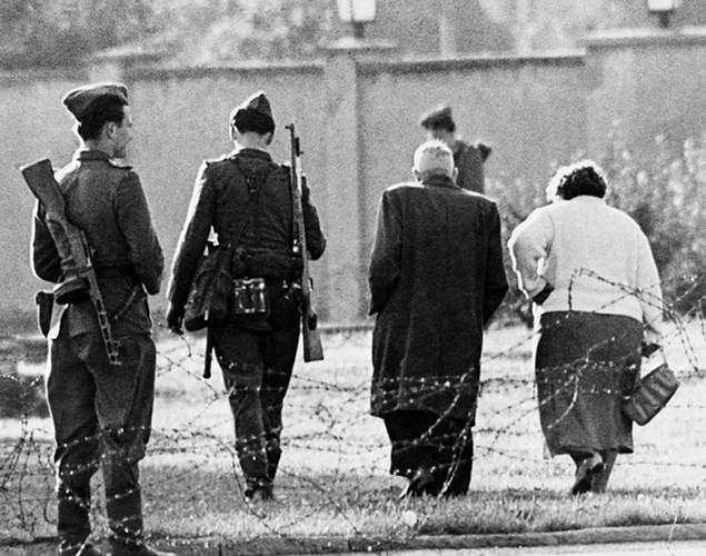 Vài thiếu niên Đông Đức với những khẩu súng đồ chơi, chơi trò đóng giả làm cảnh sát khi chúng nhìn về phía bức tường bê tông ở Bernauer Strasse năm 1961.