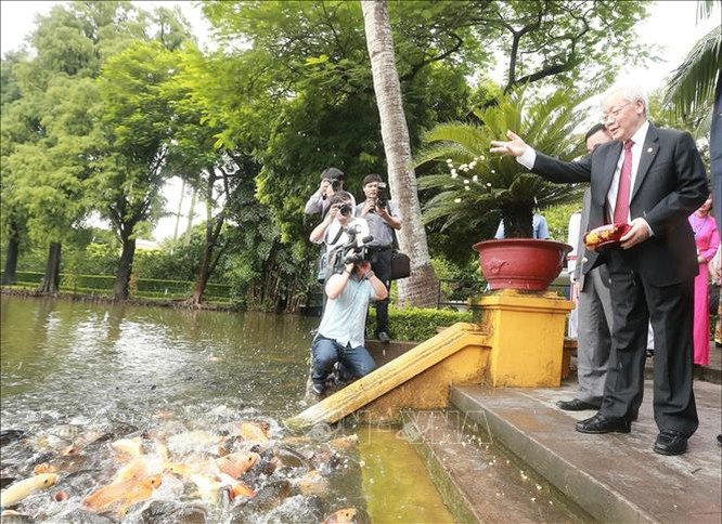 Tổng Bí thư, Chủ tịch nước Nguyễn Phú Trọng cho cá ăn tại Ao cá Bác Hồ trong khuôn viên Khu Di tích Chủ tịch Hồ Chí Minh.