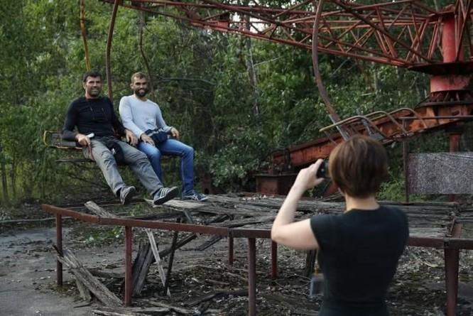 Du khách chụp ảnh lưu niệm tại nơi từng là khu vui chơi ở thị trấn Pripyat năm 2017 (Ảnh: Newsweek)