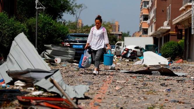 Một người dân đi qua đống hoang tàn sau trận lốc xoáy (Ảnh: CNN)