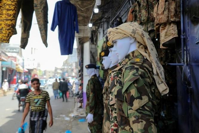 Các bộ áo lính treo bên ngoài một cửa hàng ở chợ truyền thống Taez (Ảnh: AFP)
