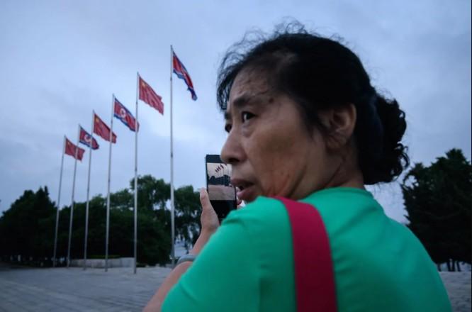 Một người phụ nữ sử dụng smartphone chụp ảnh quảng trường Kim Il Sung ở thủ đô Bình Nhưỡng (Ảnh: AFP)