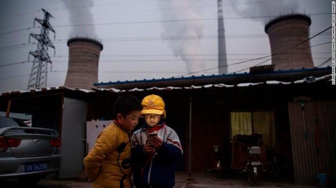 Hai cậu bé xem điện thoại di động gần một nhà máy điện than ở ngoại ô thủ đô Bắc Kinh (Ảnh: CNN)