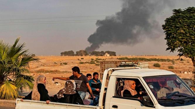 Người dân tháo chạy trong lúc cột khói lớn bốc lên từ thị trấn Ras al-Ain, Đông Bắc Syria sau đòn không kích của Thổ Nhĩ Kỳ (Ảnh: ABC)