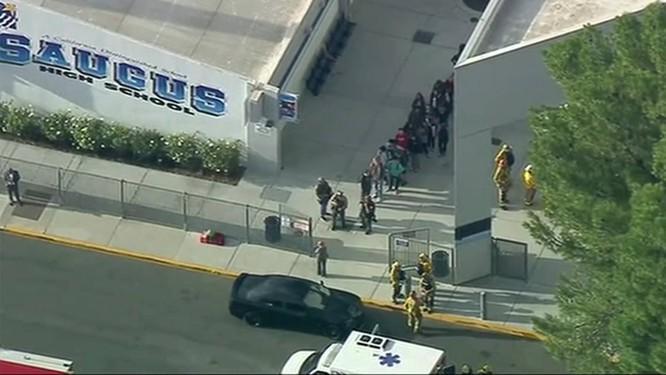 Cảnh sát vũ trang hộ tống một nhóm học sinh ra khỏi trường an toàn (Ảnh: CNN)