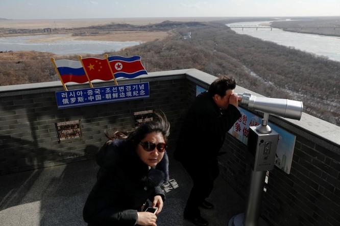 Một du khách Trung Quốc quan sát khu vực biên giới giữa Nga-Trung-Triều Tiên bằng ống nhòm (Ảnh: Reuters)