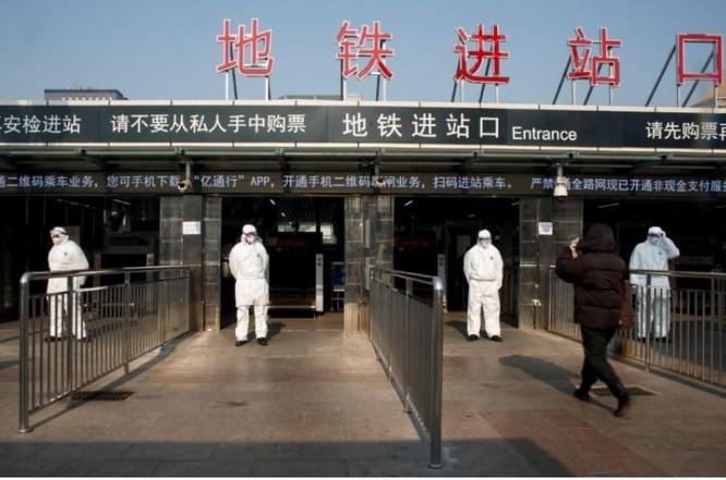 Nhân viên y tế kiểm tra thân nhiệt hành khách tại trạm xe lửa trung tâm Bắc Kinh (Ảnh: Reuters)