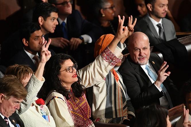 Các nhà lập pháp đảng Dân chủ giơ 3 ngón tay trong lúc ông Trump phát biểu (Ảnh: AFP)