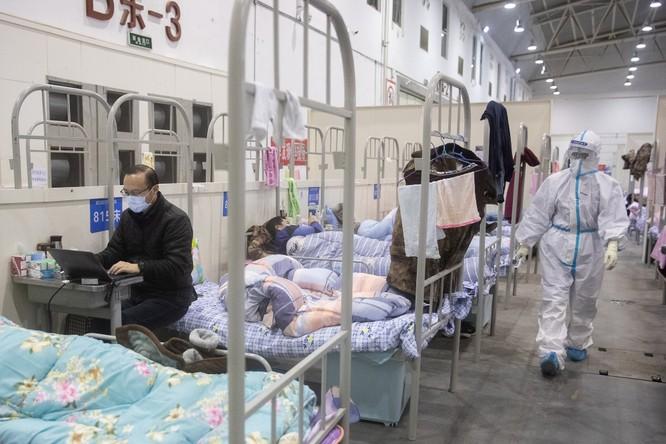 Một người bệnh chỉ xuất hiện triệu chứng nhẹ của COVID-19 đang sử dụng laptop trên dãy giường xếp dài (Ảnh: AFP)