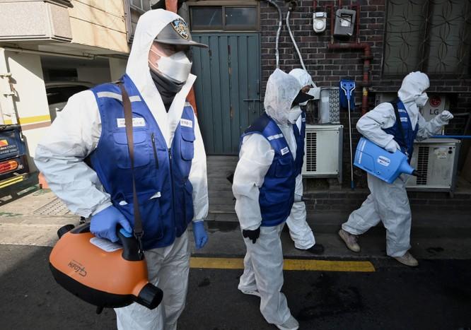 Các nhân viên phun thuốc phòng dịch tại một khu chợ ở thủ đô Seoul, Hàn Quốc (Ảnh: AFP)