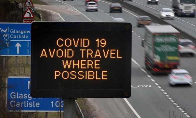 Biển báo khuyến cáo hạn chế di chuyển thời dịch COVID-19 trên một tuyến đường ở Anh (Ảnh: Guardian)