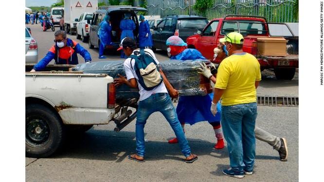 Nhóm người mặc đồ bảo hộ khiêng quan tài lên xe trước cổng một bệnh viện ở Guayaquil (Ảnh: CNN)