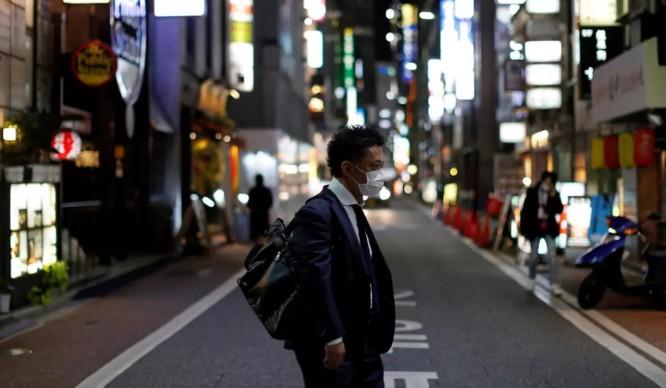 Một người đàn ông mang khẩu trang đi bộ ở khu Ginza, thủ đô Tokyo, Nhật Bản (France24)