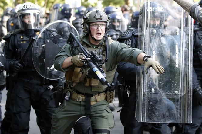 Cảnh sát chống bạo động cố gắng giải tán người biểu tình gần Nhà Trắng (Ảnh: AP)