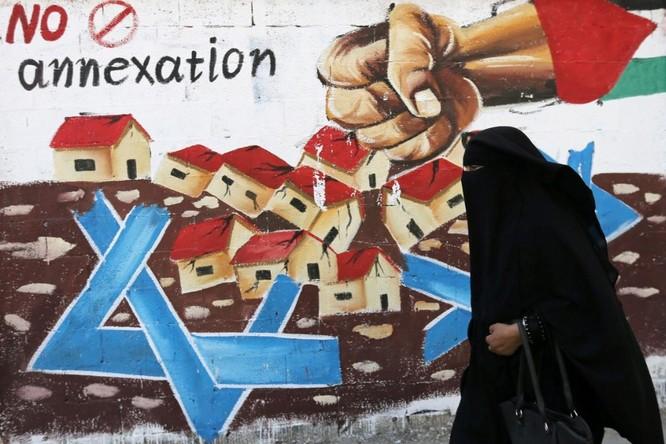 Một phụ nữ Palestine đi qua bức tranh cổ động chống kế hoạch sát nhập nhiều phần khu Bờ Tây của Israel (Ảnh: Reuters)