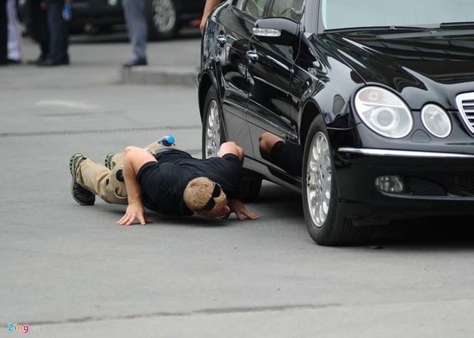Đặc vụ Mỹ nằm rạp xuống đất để kiểm tra xe. Việc này được tiến hành thường xuyên, nhiều lần trước khi đoàn xe của Tổng thống Obama xuất phát.