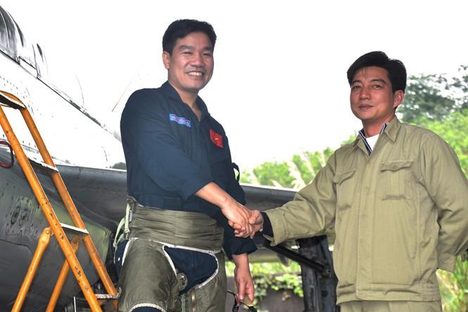 Phi công Nguyễn Hữu Cường (bìa trái, một trong 2 phi công mất tích) được nhân viên kỹ thuật đón xuống sân bay khi kết thúc chuyến bay huấn luyện bằng Mig-21 tại sân bay quân sự Yên Bái, tháng 2.2013 ẢNH: MAI THANH HẢI