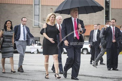 Ông Trump che ô để bảo vệ mái tóc của mình. (Nguồn: AP).