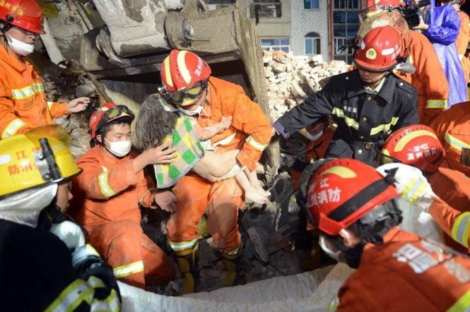Bé Wu đã được cứu sống nhờ vào sự che chở của người cha - Ảnh: AFP