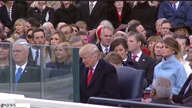Ông Trump ngồi ở hàng ghế đầu trên lễ đài, phía trước có tấm kính chắn bảo vệ.