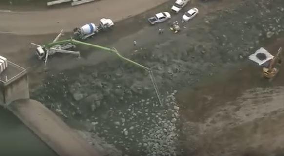 Khu vực chân đập đang được gia cố bằng đá hộc và bê tông.