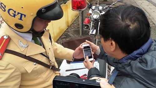 Người vi phạm xem lại hình ảnh từ điện thoại di động của CSGT
