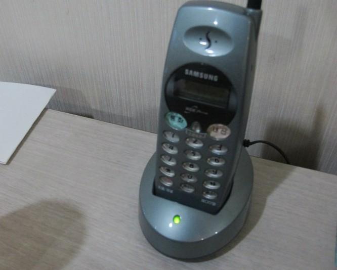 Trên bàn lắp một chiếc điện thoại Samsung đời cổ.