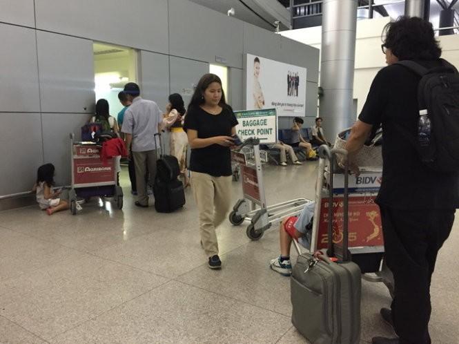 Hành khách đi nước ngoài chờ kiểm tra hành lý ký gửi tại phòng soi của hải quan sân bay quốc tế Tân Sơn Nhất chiều 7-4