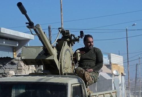 Một tay súng ủng hộ chính phủ Syria tại một ngôi làng vừa thoát khỏi tay IS ở ngoại ô Aleppo.