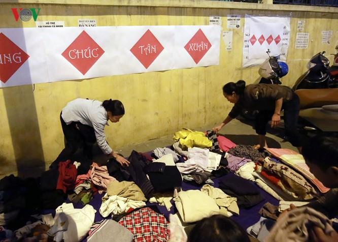 Những bộ quần áo được giặt sạch sẽ, gấp gọn ghẽ phía sau quầy bánh chưng để người lao động nghèo lựa chọn.