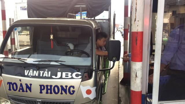 ... sau đó anh này tiếp tục đi vào trạm, tắt máy xe và đếm từng tờ tiền lẻ để mua vé.