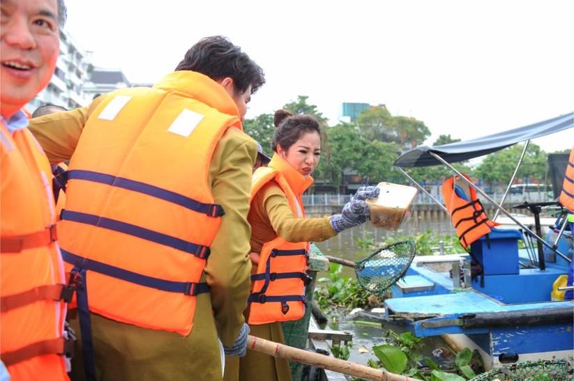 Thúy Nga tự tay vớt rác trên kênh Thị Nghè. Người đẹp diện chiếc áo dài Việt Hùng được làm bằng chất liệu thân thiện với môi trường